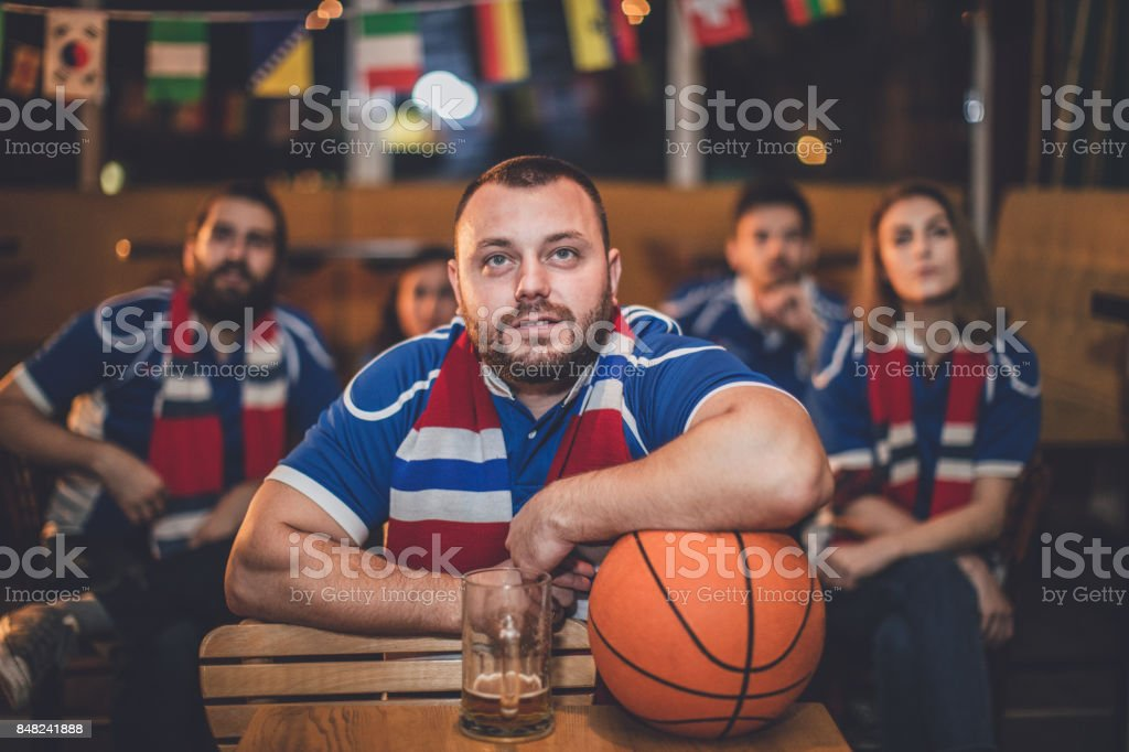 Group of friends watching game in a pub, focus on one man in front...