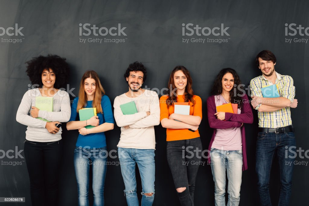 Friends with books in a row against blackboard stock photo