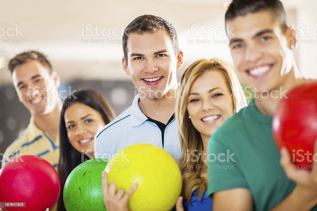 Friends with bowling balls in a row. royalty-free stock photo