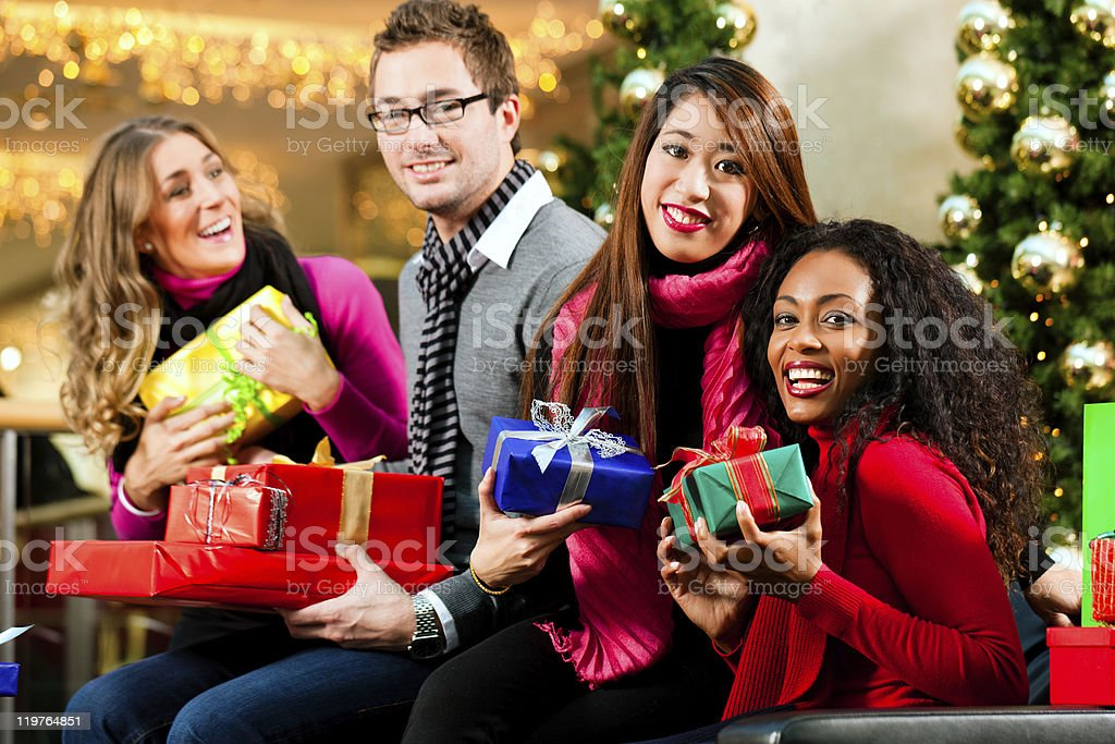 Friends with Christmas presents and bags in mall stock photo