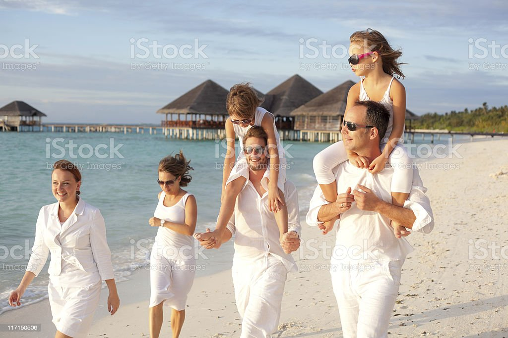 friends with kids walking along beach royalty-free stock photo