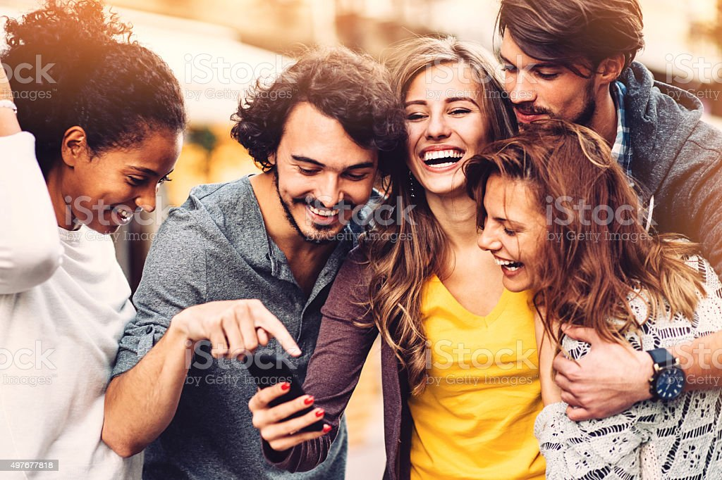 Friends with phone outdoors stock photo