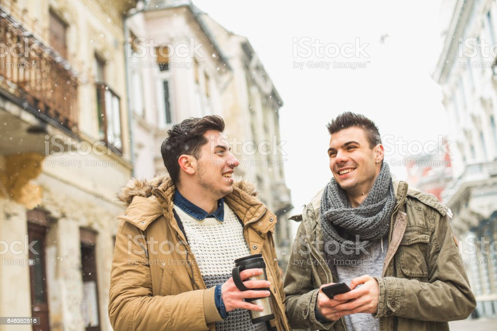 Friends with smart phone and travel mug stock photo