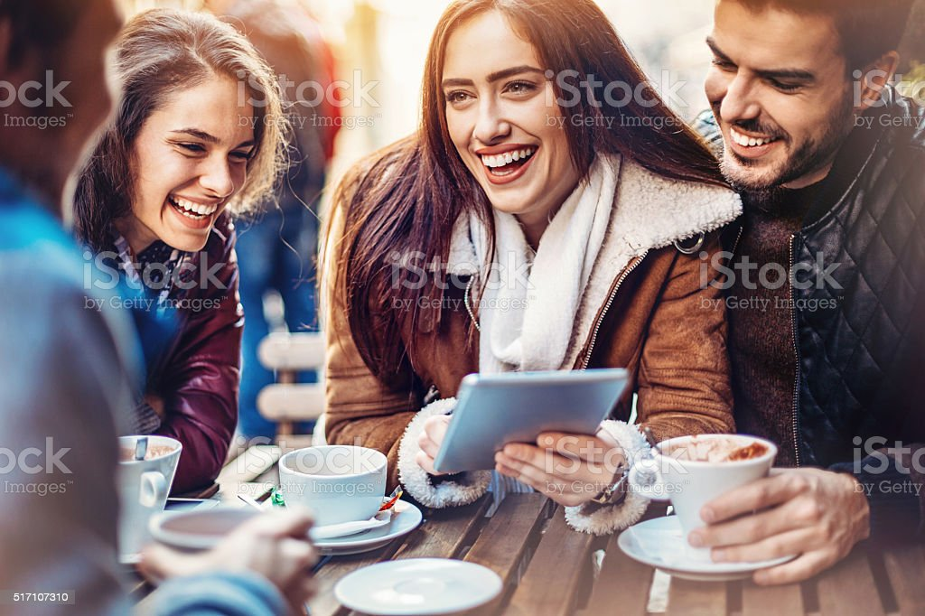 Friends with tablet and hot drinks stock photo