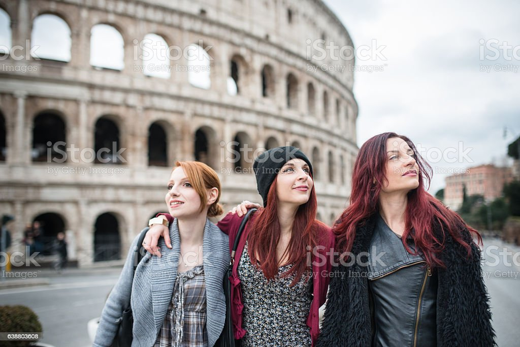 friends woman walking embraced in rome stock photo