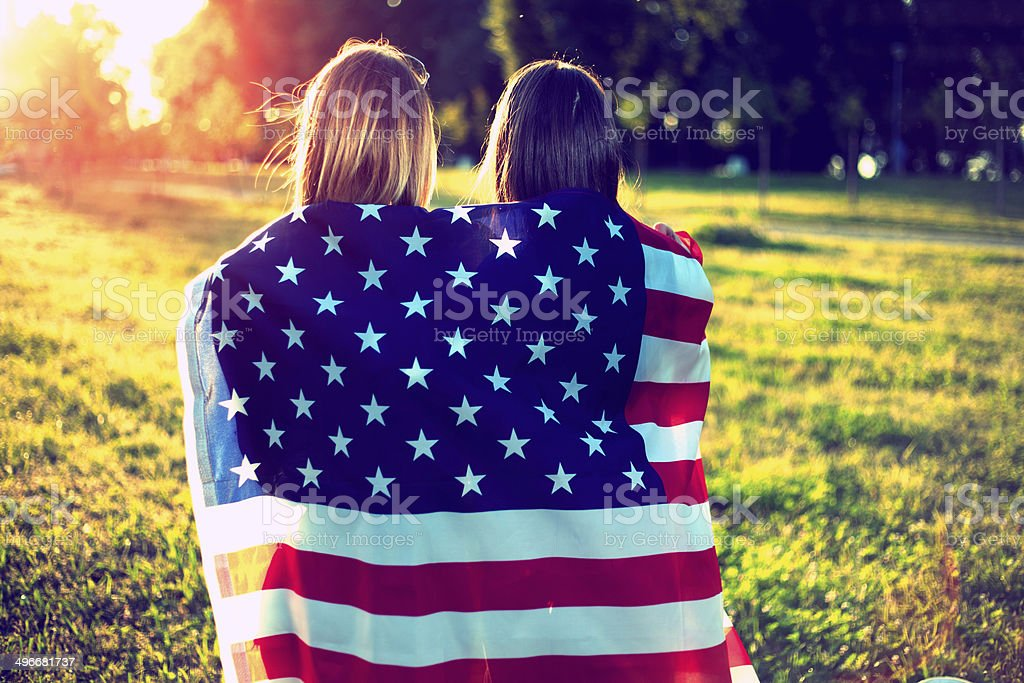 Friends wrapped in the American flag stock photo