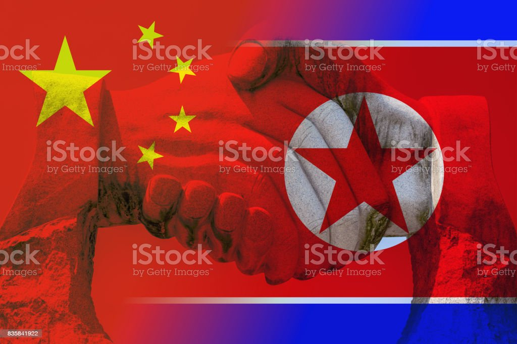 Friendship between China and North Korea with handshake stock photo