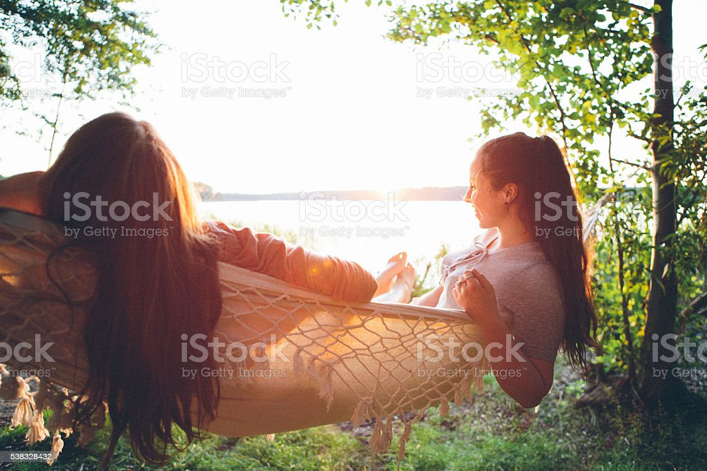 friendship: rear view, two young woman relax in a hammock stock photo