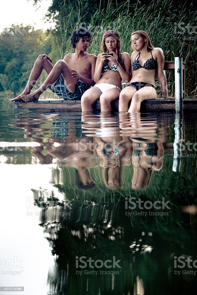 friendship: teenagers relax on a jetty with legs into water royalty-free stock photo