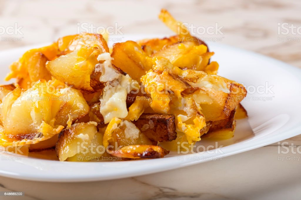 Fries with smashed eggs on white plate stock photo