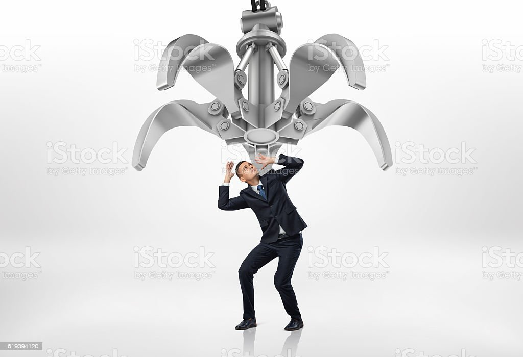 Frightened businessman in protective pose looking up at giant mechanical stock photo