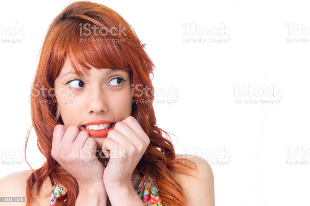 Frightened girl looks to the side and hands are close to face. Redhead woman is wearing a colorful summer dress. Fashion and style. Vacation and summer. stock photo
