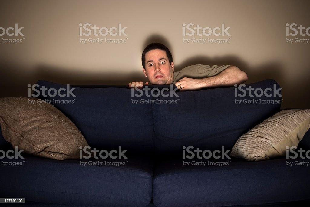 Frightened man hides behind sofa watching TV royalty-free stock photo