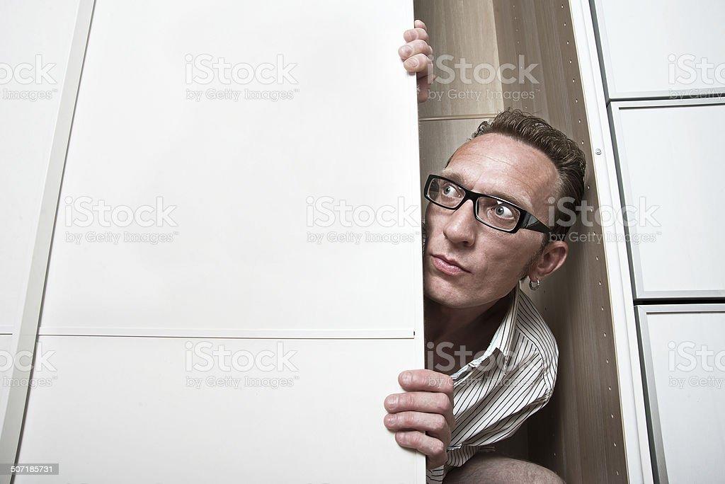 Frightened man peep out white wardrobe. stock photo
