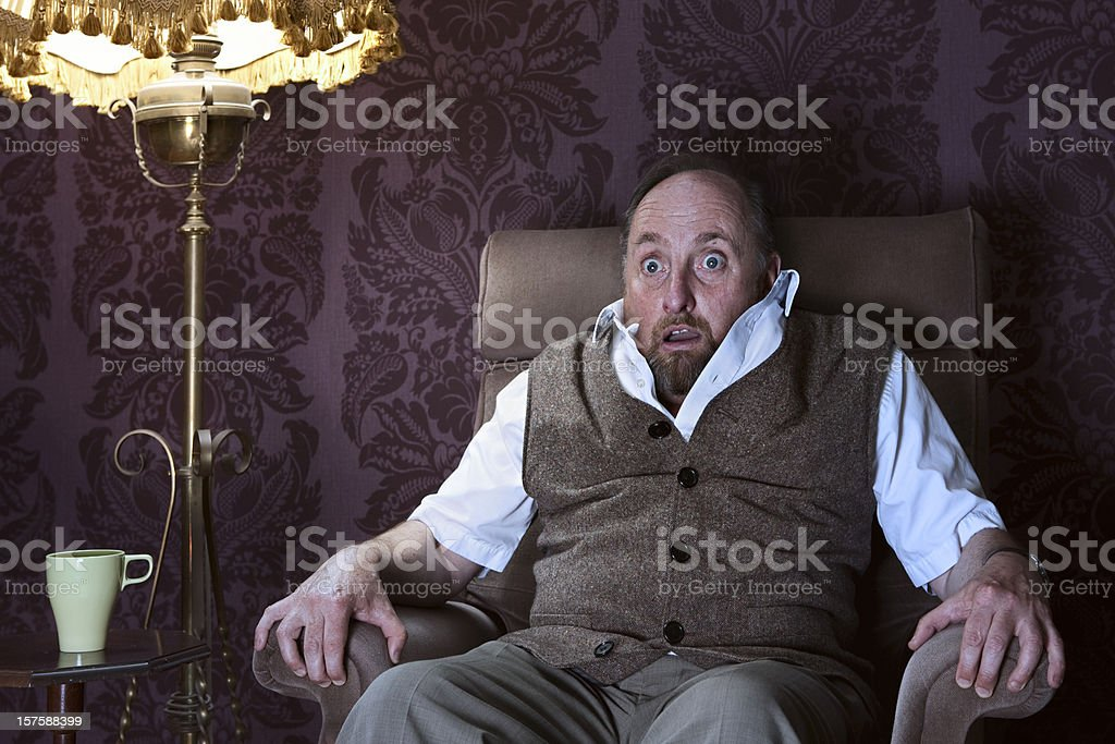 Frightened man watching a horror on TV stock photo