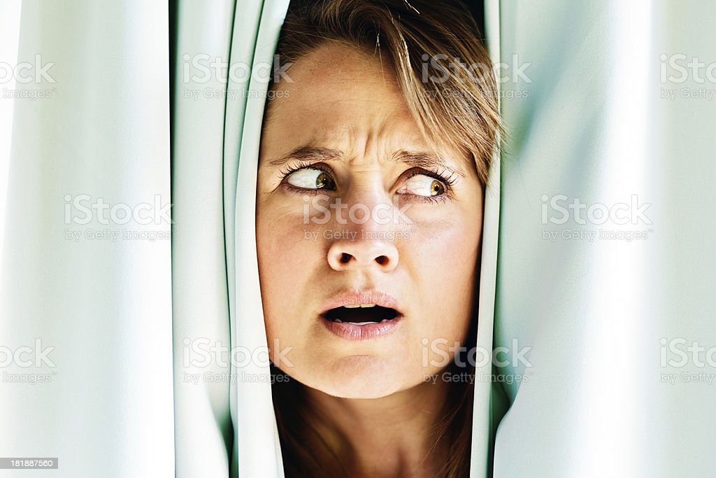 Frightened, nervous blonde peeping sideways through blue drapes royalty-free stock photo