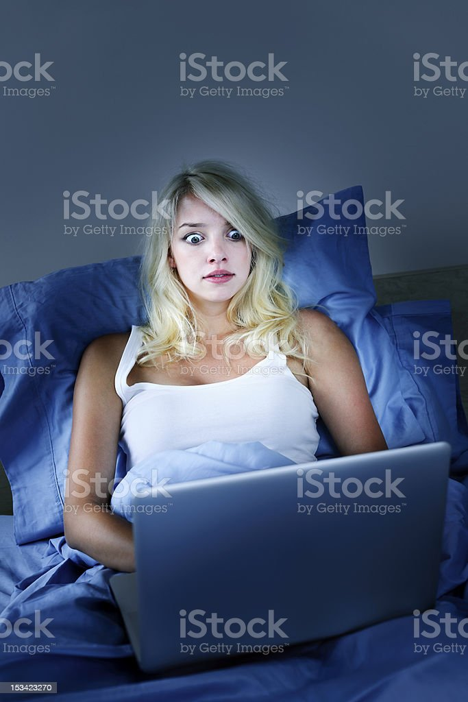 Frightened woman with computer at night stock photo