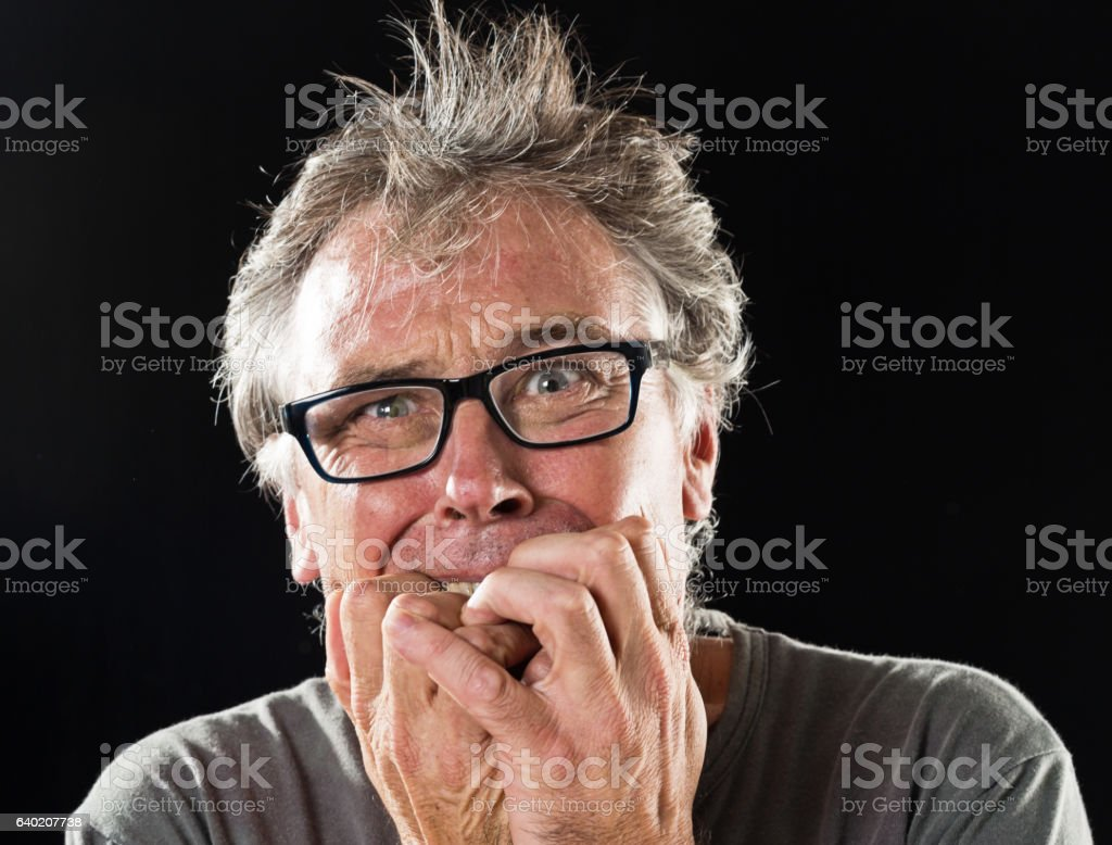 Frightened worried mans bites his nails anxiously stock photo