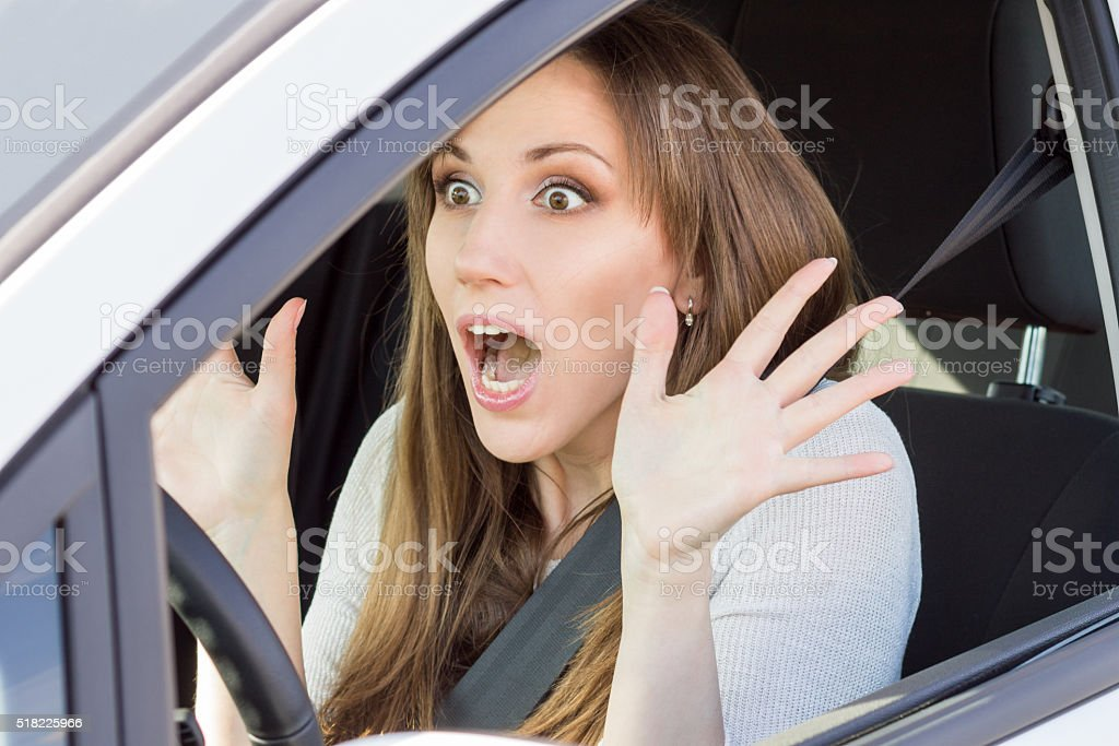 Frightened young car driver woman look straight stock photo