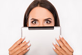 Frightened young woman hiding face behind the tablet