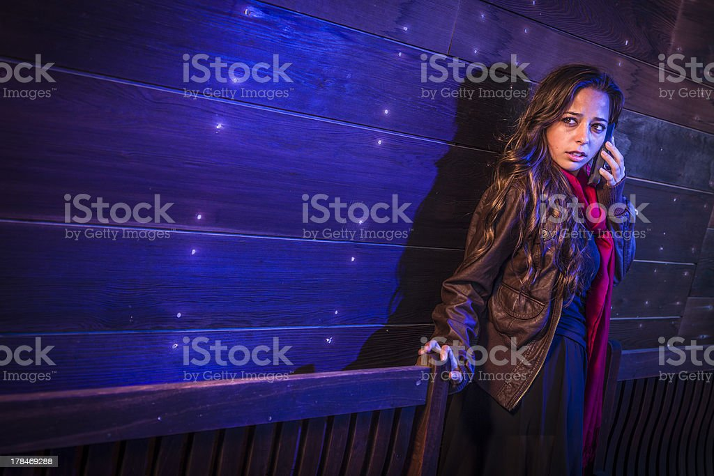 Frightened Young Woman in Dark Walkway Using Cell Phone royalty-free stock photo