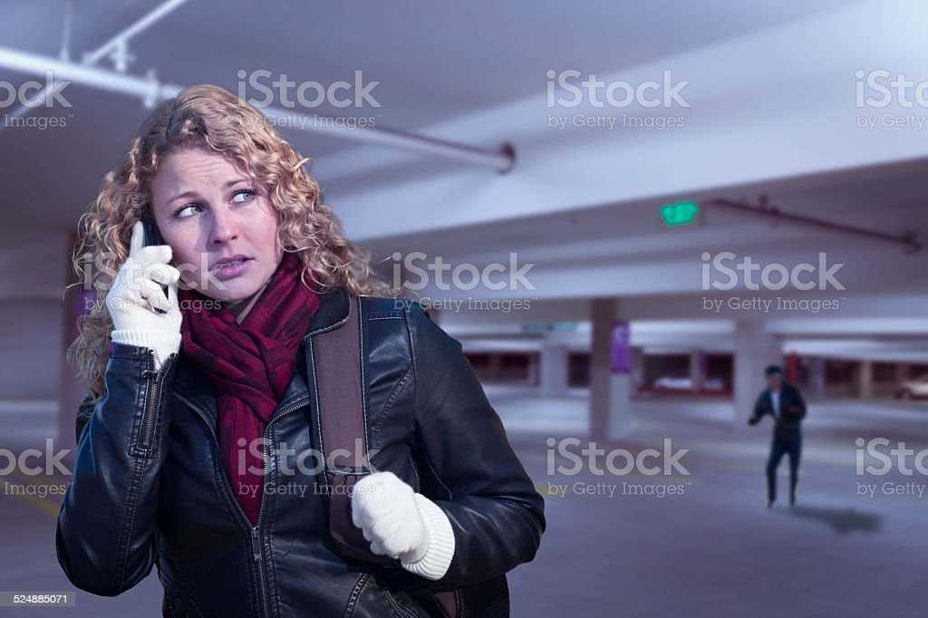 Frightened Young Woman On Cell Phone in Parking Structure stock photo