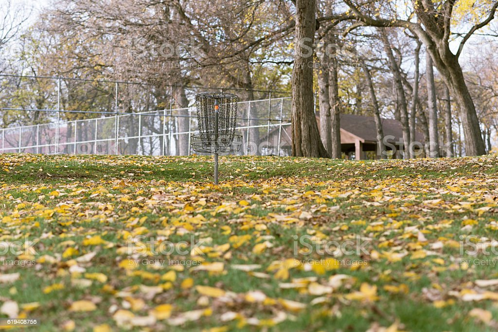 Frisbee golf basket in park during autumn stock photo