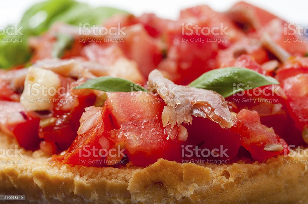 Friselle with fresh tomatoes and anchovies seasoned with olive oil stock photo