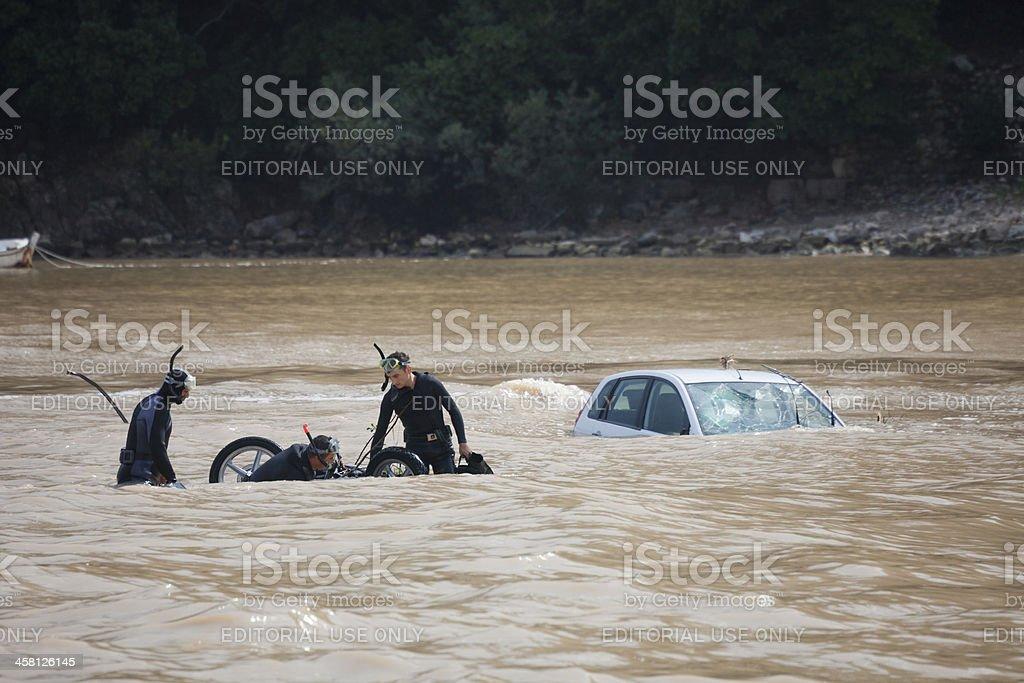 Frogmen recovering motorcycle near sunken car stock photo