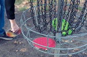 Frolf basket hole, with hand picking up disc in background.