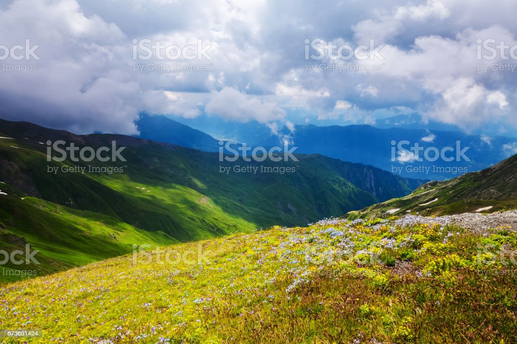 From storm cloudy sky sun's rays illuminate the magical landscapes, green meadows and mountains. Upper Svaneti, Georgia, Europe. stock photo