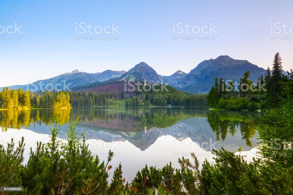 From the edge of the coast with beautiful green trees are seen mountain expanses, mesmerizing lake view and wonderful sky. stock photo