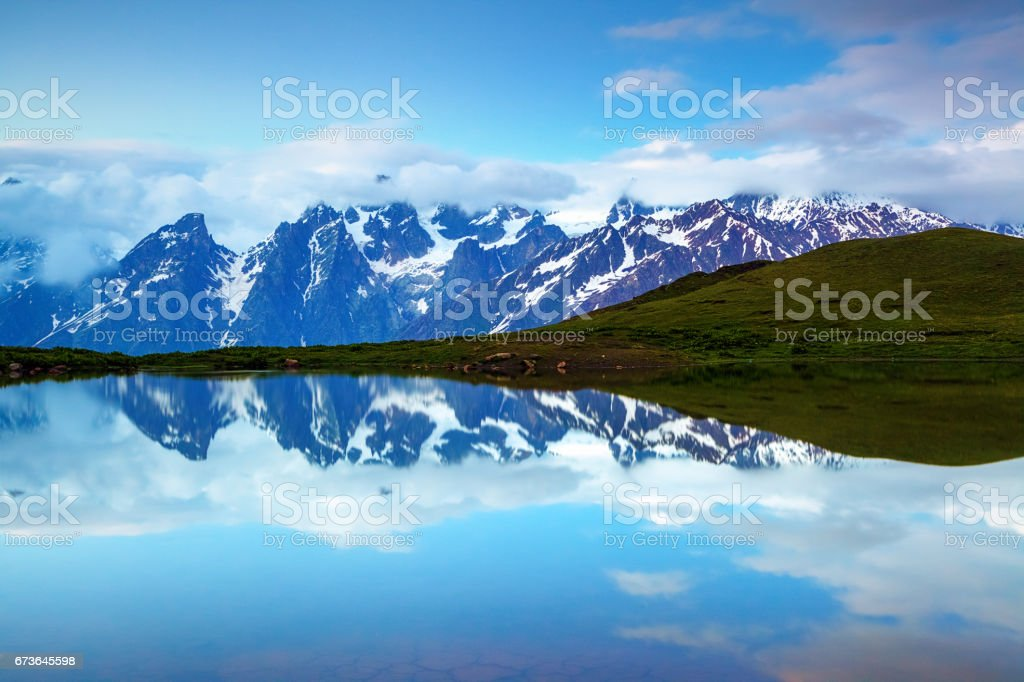 From the green lawn opens panoramic view on a fantastic high mountain lake, rocky mountains and beautiful cloudy sky. stock photo