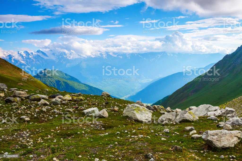 From the lawn in the rocks open fantastic views of the highest mountains in the clouds, scenic meadows and sunlight. stock photo