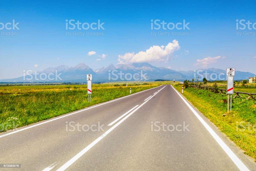 From the lonely highway there is a view of the incredible mountains with peaks hidden by clouds and endless green fields in fantastic sunny day. stock photo