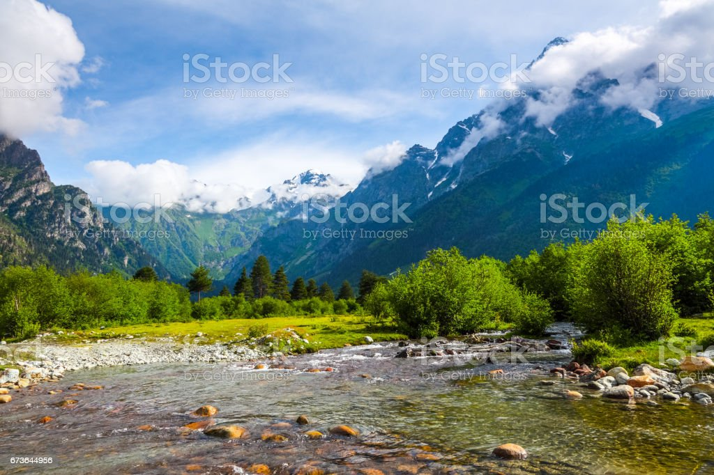 From the river shore, covered with stones, opens view on fantastic glacier and steep rocky mountains with green meadows, which are covered with snow. stock photo