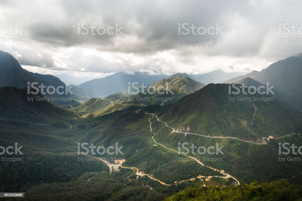 From the top of the O Quy Ho Pass, look down the winding road on a cliff in Sapa, Lao Cai, Vietnam. stock photo