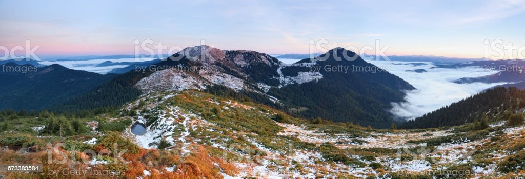 From the valley covered with snow the fantastic panorama is opened to high mountains, lake and fog in autumn morning. stock photo