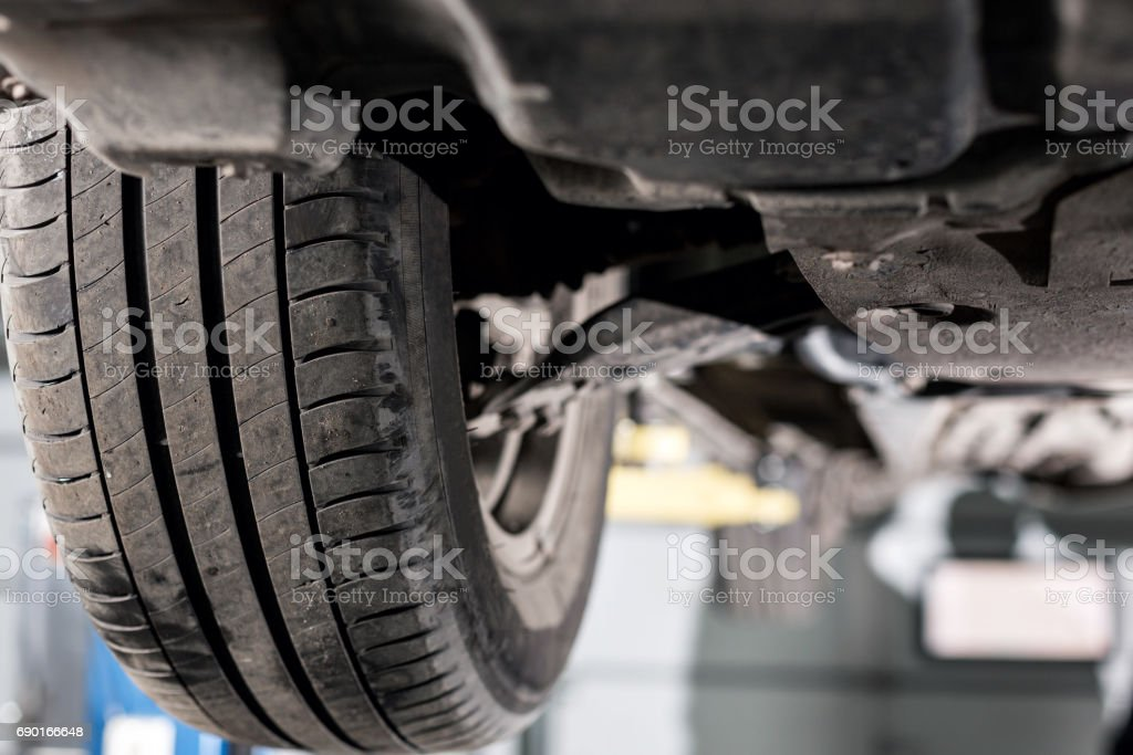 front car suspension. the garage mechanic raised the car on the lift stock photo