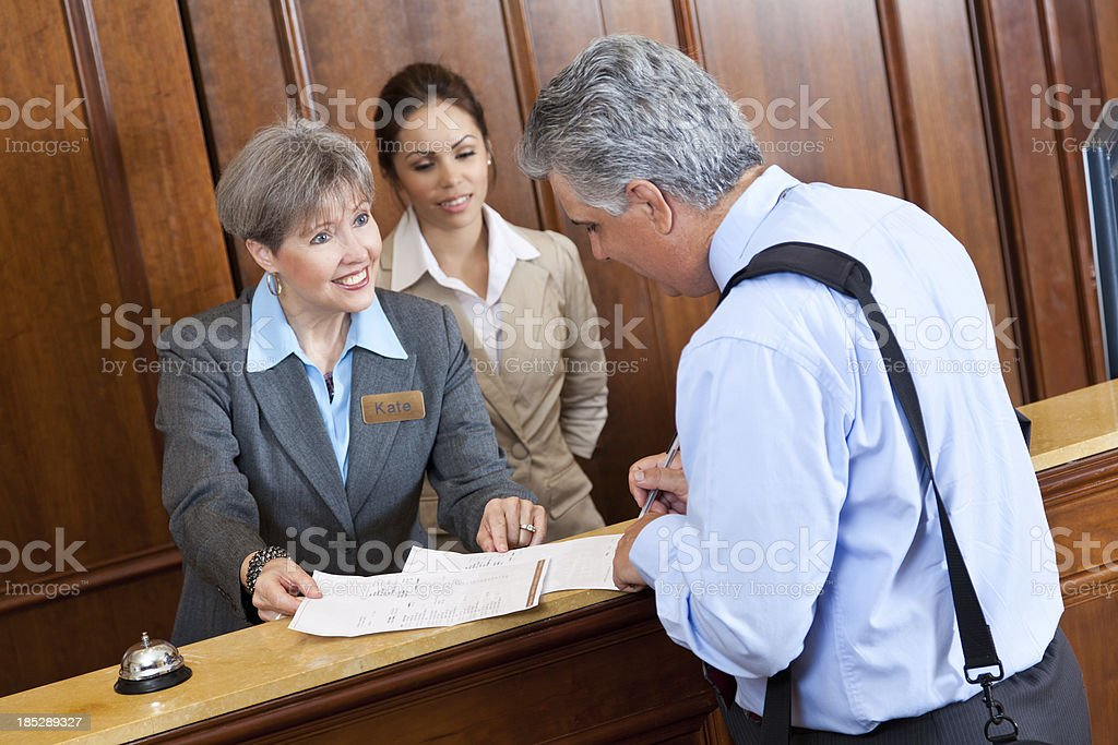 Front desk worker showing hotel bill to guest royalty-free stock photo