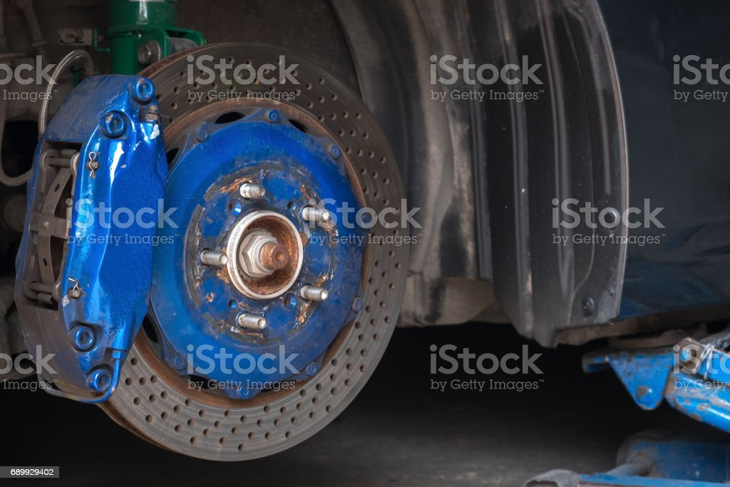 Front disc brake on car in process of new tire replacement stock photo