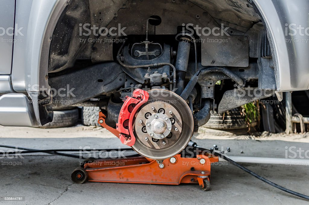 Front disc brake on car in process of tire replacement. stock photo