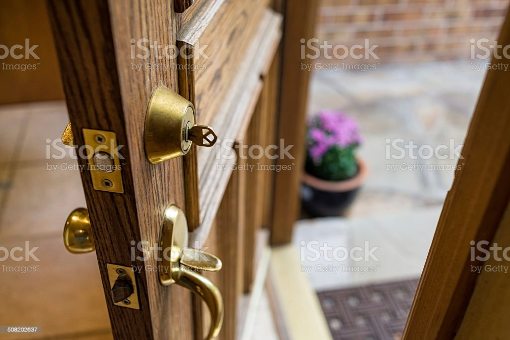 Front Door Left Open with Key in Lock stock photo
