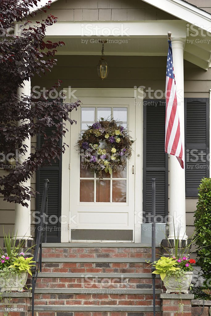 Front door of a house with wreath and American flag stock photo