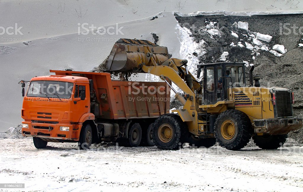 Front End Loader Unloading Scoop into Dump Truck stock photo