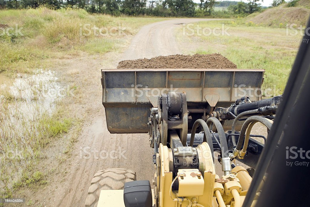 Front End Loader with Full Bucket Traveling on Dirt Road royalty-free stock photo