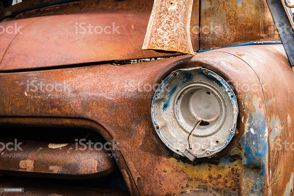 Front headlight of an rusty car in garage stock photo