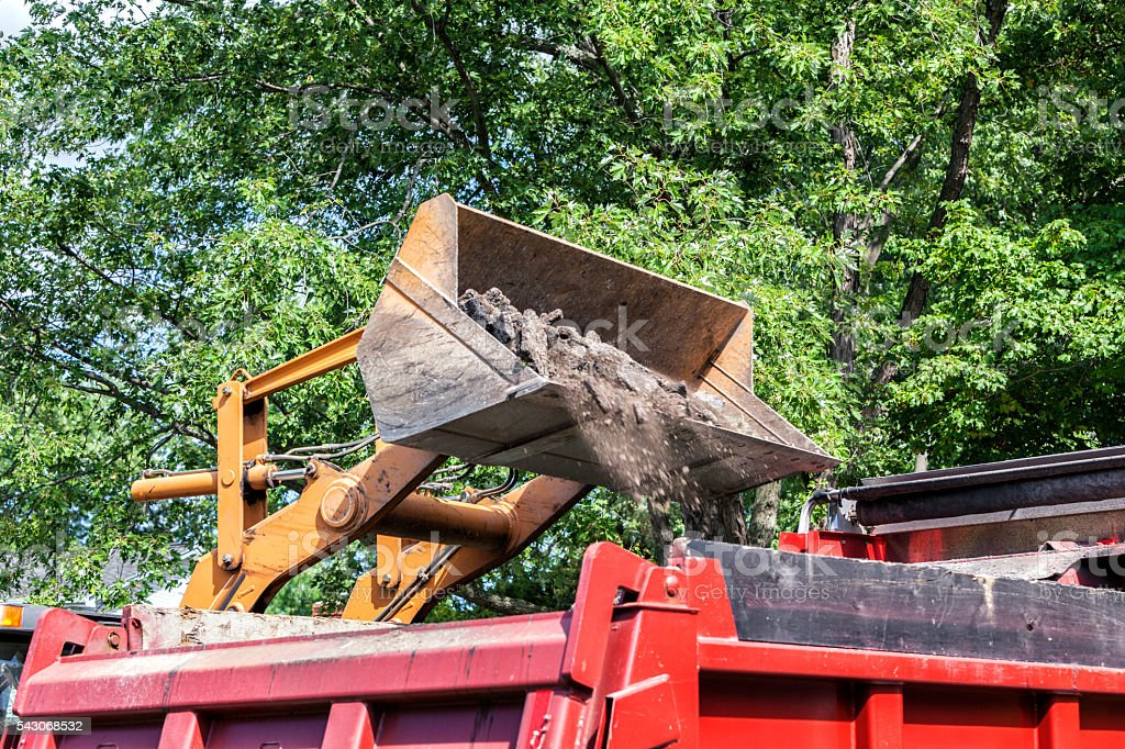 Front Loader Bucket Dropping Asphalt Road Rubble Into Dump Truck stock photo