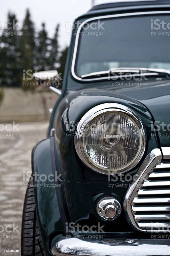Front of a dark green mini cooper with one headlight shown royalty-free stock photo