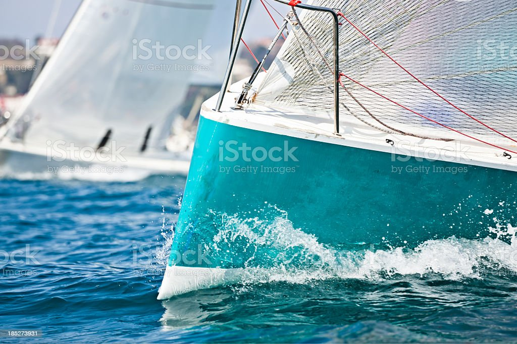 Front of a sailing boat in a regatta with waves hitting it stock photo
